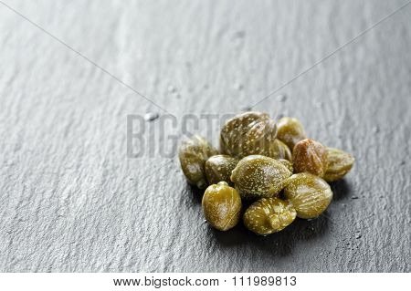 marinated capers on slate board