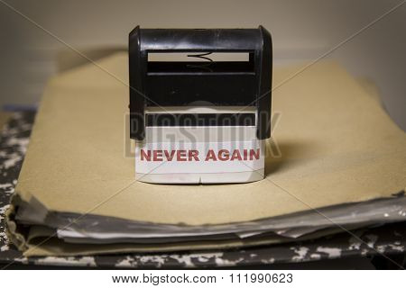 Never Again Slogan On A Stamp Over Big Folder Of Paperwork