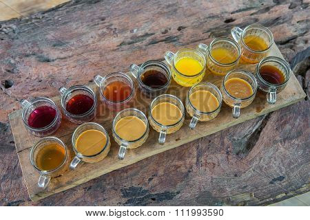 Coffee with multiple assorted types and flavors of coffee and tea in identical mugs for degustation on farm Bali island