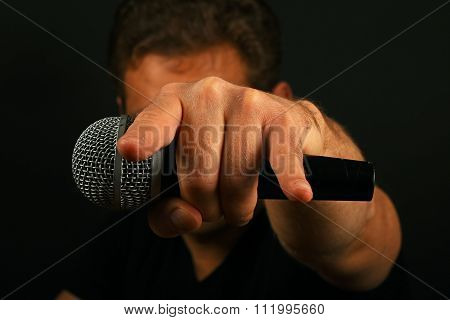 Hand With Microphone And Devil Horns On Black