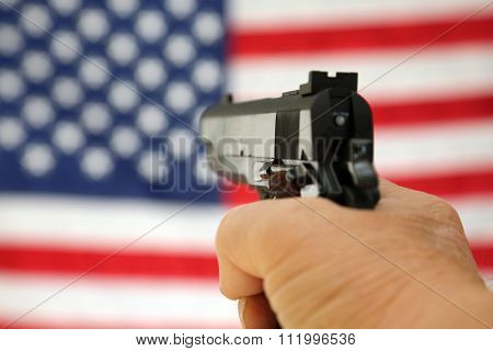 A pistol pointed towards an American Flag, shot with shallow depth of field with the focus on the gun. The American flag is slightly out of focus. 2nd amendment rights. right to bare arms.