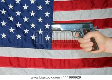 A .45 pistol is held in front of an American Flag. Represents Americas 2nd Amendment, the right to bare arms. Civil Liberty. Personal Protection. Protection of life and property. Gun Control. Guns.