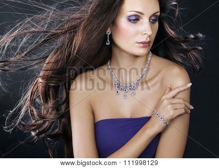 Beautiful woman with jewellery on dark background