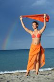 Young Brunette Woman In Orange Bikini And Pareo Holding Scarf Over Her Head And Smiling poster