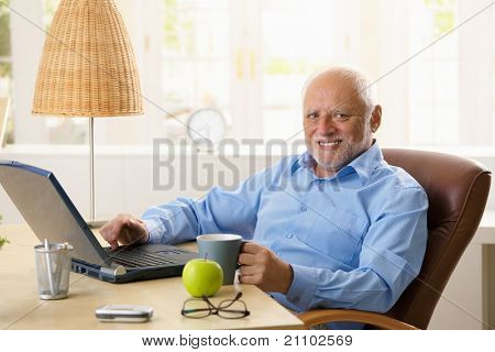 Portrait of happy senior man sitting at desk using laptop computer at home, smiling at camera.