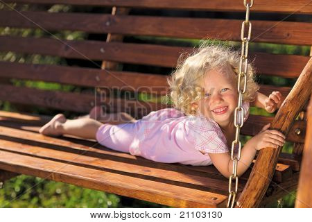 Cute Little Girl With Blond Curly Hair Playing On Wooden Chain S