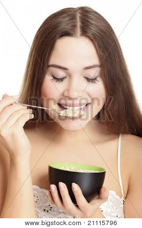 portrait of young caucasian woman eating cereals, isolated over white background