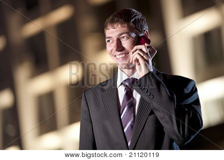 happy businessman talking on cell phone at night city in the background