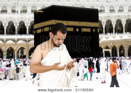 Muslim pilgrims in white traditional clothes, praying at Kaaba in Makkah