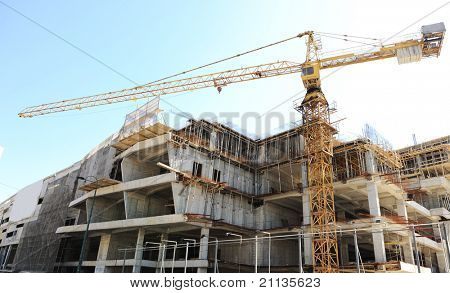 Buildings under construction and cranes under a blue sky