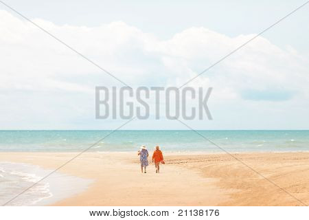 couple of womens walking on the beach