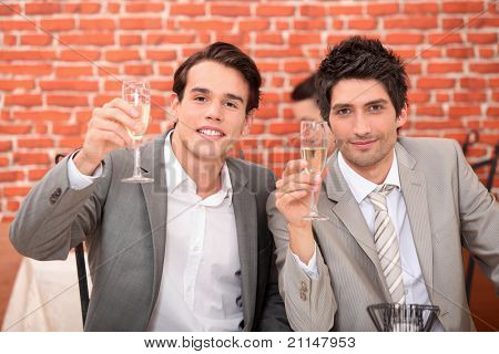 Young men in suits drinking champagne