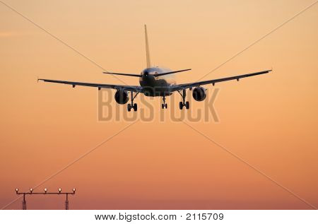 Airliner Landing At Sunset