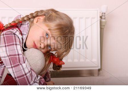 Sad girl sitting near heater. Children depression.