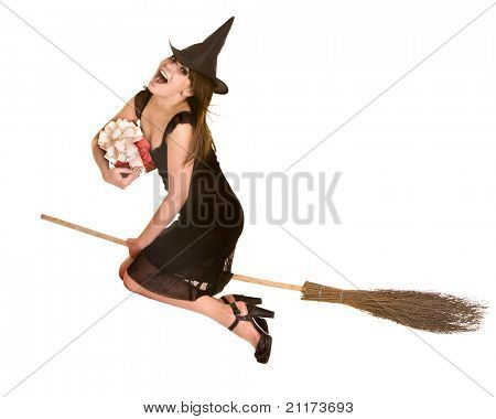 Halloween witch blond in black dress and hat fly on broom with red gift box.Isolated.