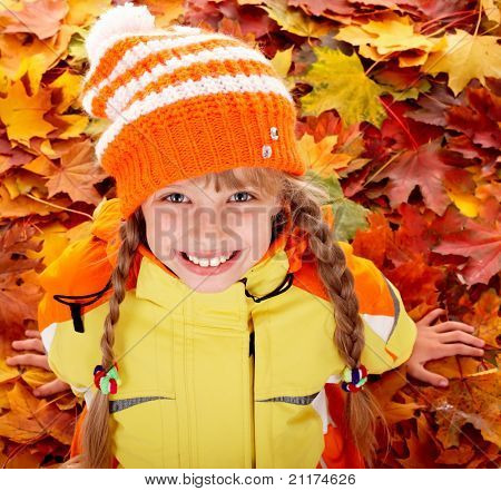 Girl in autumn orange  hat on leaf background. Outdoor.