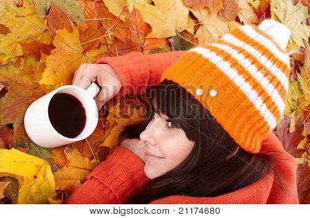 Girl in autumn orange leaves with cup coffee. Outdoor.