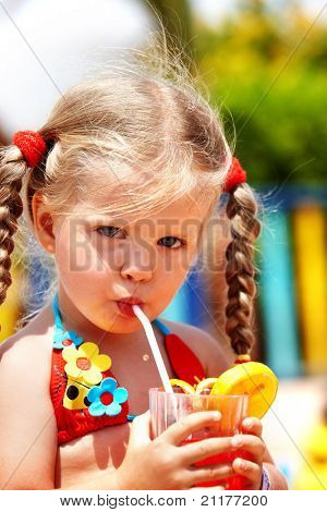 Child girl in sunglasses and red bikini drink orange juice.