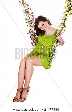 Beautiful girl swinging on flower swing. Isolated.
