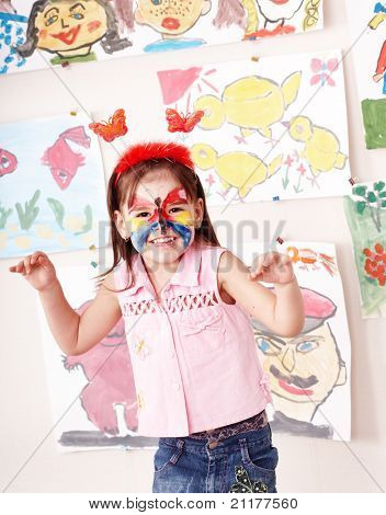 Child with paint of face in play room. Make up.