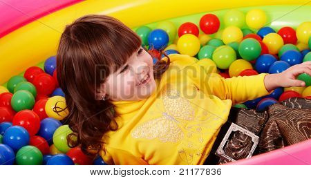 Preschooler girl with ball in play room. Childcare.