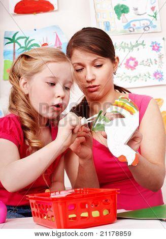 Children with teacher in play room. Preschooler.