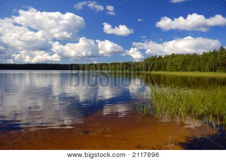 Lake In-Field. A Bright Summer Sun. White Clouds. Blue Water.