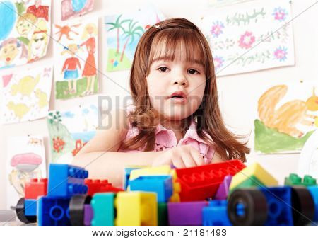 Child preschooler with construction set in play room.