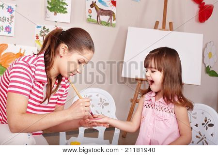 Little girl  making hand prints.