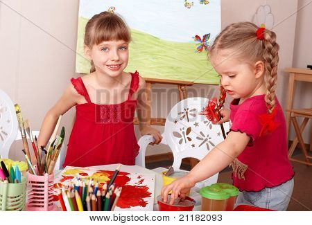 Children painting colour paints in preschool.