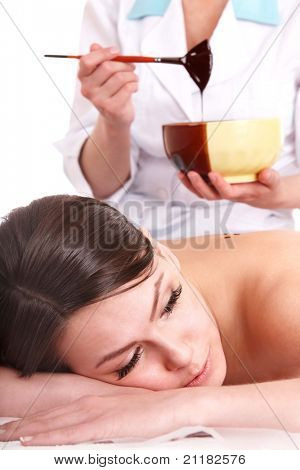 Young woman having chocolate body mask apply by beautician.