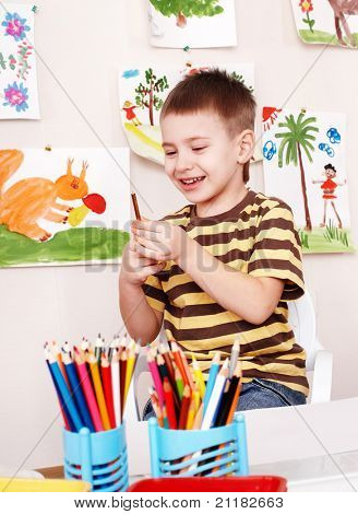 Little boy with pencil in play room.