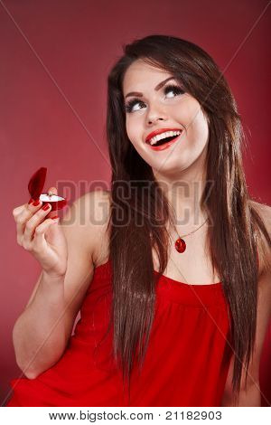 Young woman with  jewelery gift box on red background. Valentines day.