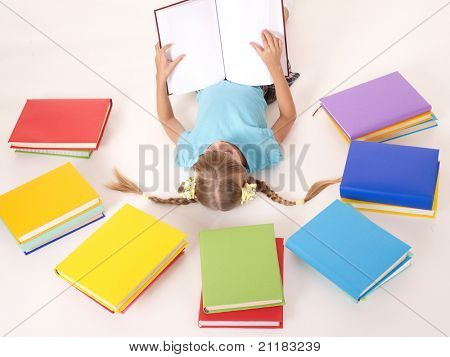 Little girl  with open book lying on floor.