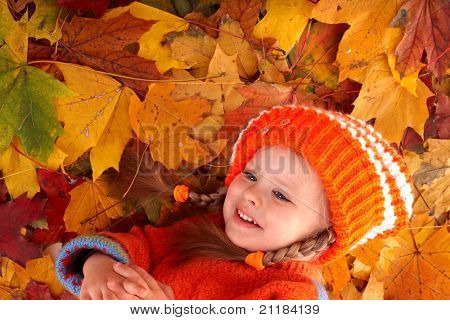 Little girl in autumn orange  leaves. Outdoor.