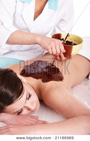 Young woman having chocolate body mask.