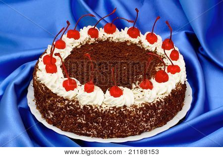 Chocolate Cake With Cherries  On A Background Of Blue Silk