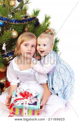 baby girl hugging her sister under the christmas tre