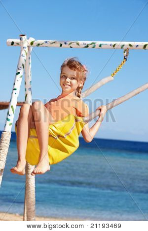 Happy little girl swinging on  swing .