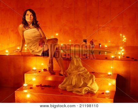 Woman sitting on edge of sauna.