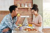 Hungry Young Mixed Race Man Eats Apple As Waits When His Wife Cooks Dinner. Curly Beautiful Woman Ma poster