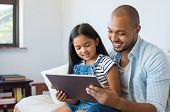 African father and smiling daughter sitting on sofa using digital tablet. Happy dad watching cartoon poster