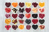 Food for healthy living with fruit, grains, vegetables and pulses in heart shaped dishes on rustic  poster