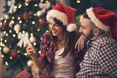Young pair in love at Christmas night looking at cell phone together poster