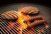 stock photo of hot dogs  - Hamburger patties and hot dogs on the grill under flaming coals - JPG