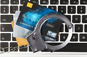 Handcuffs and credit cards on laptop keyboard, close up poster