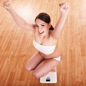 Happy beautiful girl on scales.  Weight-loss.
