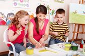 image of child development  - Children with teacher draw paints in play room - JPG
