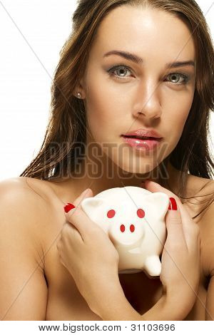 beautiful woman holding piggy bank