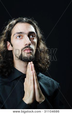 Joven orando en la oscuridad